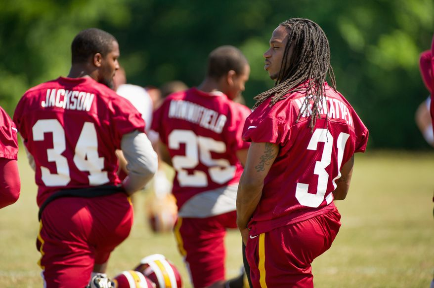 Redskins safeties Brandon Meriweather (right) and Tanard Jackson stretch during drills Thursday. Both were brought in during the offseason. (Associated Press)