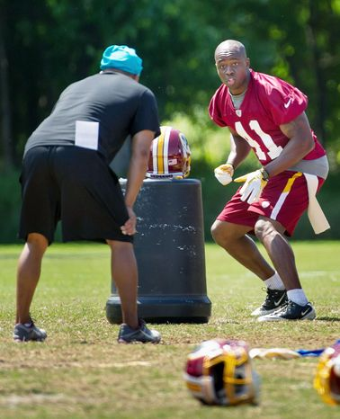 Redskins safety Madieu Williams, who played last season with San Francisco, runs a drill with a member of the coaching staff. (Andrew Harnik/The Washington Times)