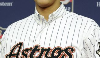 Major League Baseball's No. 1 draft pick Carlos Correa, 17, from Puerto Rico, smiles in his new jersey during a news conference after signing with the Houston Astros on Thursday, June 7, 2012, in Houston. (AP Photo/Pat Sullivan)
