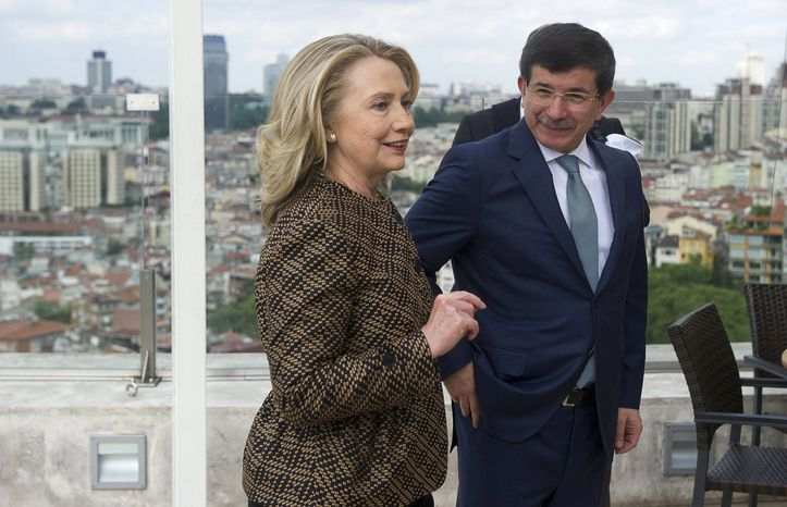 Turkish Foreign Minister Ahmet Davutoglu, right, and U.S. Secretary of State Hillary Rodham Clinton arrive for a meeting in Istanbul Thursday, June 7, 2012. (AP Photo/Saul Loeb, Pool)