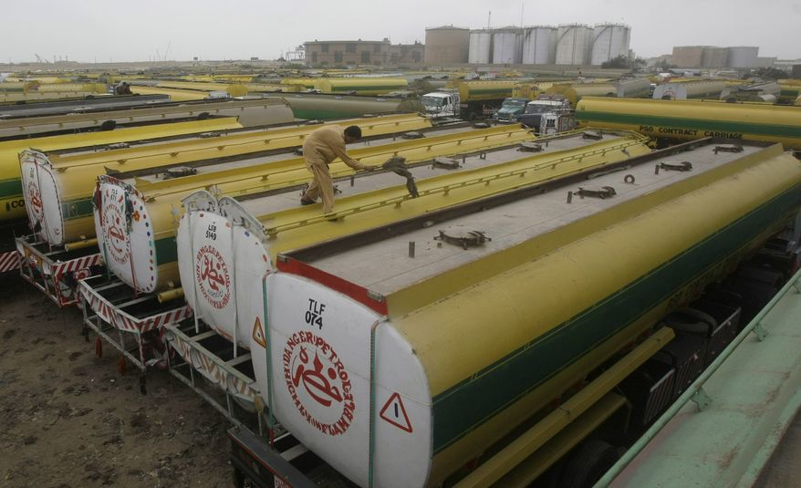 In this Wednesday, June 6, 2012, photo, a Pakistani man cleans the roof of an oil tanker that was used to transport NATO fuel supplies to Afghanistan, and parked with other tankers in a compound in Karachi, Pakistan. (AP Photo/Fareed Khan)