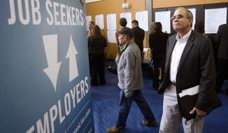 **FILE** Job seeker Alan Shull (right) attends a job fair in Portland, Ore., on April 24, 2012. (Associated Press)