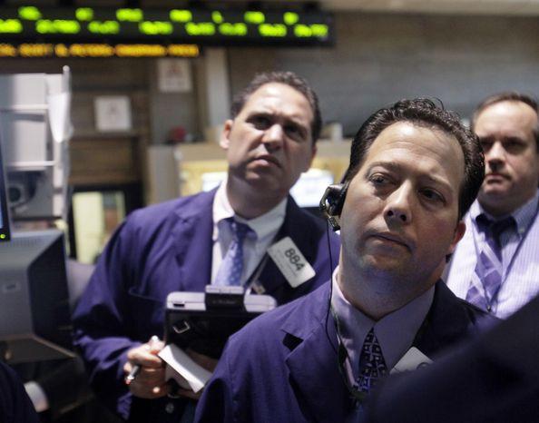 Traders work June 7, 2012, on the floor of the New York Stock Exchange. (Associated Press)