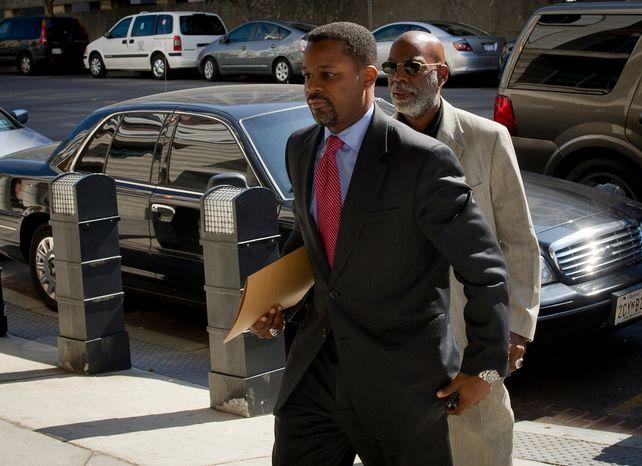 Former D.C. Council Chairman Kwame R. Brown (left) enters the E. Barrett Prettyman Federal Courthouse for his plea hearing in Washington, D.C., Friday, June 8, 2012. (Rod Lamkey Jr/The Washington Times)