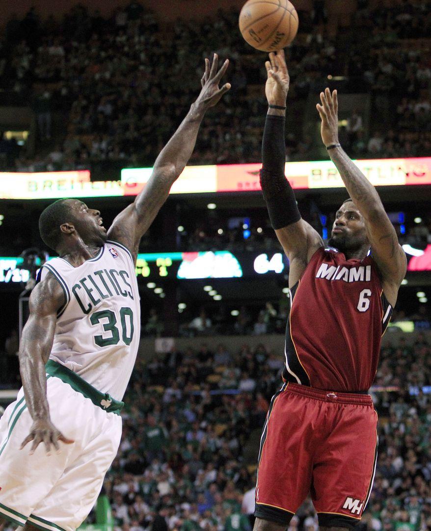 Miami Heat forward LeBron James shoots against Boston Celtics forward Brandon Bass during the fourth quarter in Game 6 of the Eastern Conference finals, Thursday, June 7, 2012, in Boston. Miami won 98-79. (AP Photo/Elise Amendola)