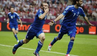 Greece's Dimitris Salpigidis, left front, celebrates after scoring the equalizer during the Euro 2012 championship Group A match between Poland and Greece in Warsaw, Poland, on Friday, June 8, 2012. (AP Photo/Matt Dunham)