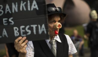 "**FILE** A demonstrator holds a banner reading in Spanish ""Bankia is a wild animal"" during a demonstration June 2, 2012, next to a Bankia bank branch in Barcelona. (Associated Press)"