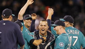 Seattle Mariners catcher Jesus Montero, center, celebrates a no-hitter with teammates, including closer Tom Wilhelmsen, left, after the final out against the Los Angeles Dodgers on Friday, June 8, 2012, in Seattle. The Mariners won 1-0, and six pitchers combined on the feat. (AP Photo/Elaine Thompson)