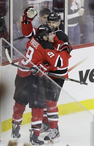 New Jersey Devils' Zach Parise celebrates with teammate Travis Zajac after scoring in the first period during Game 5 of the NHL hockey Stanley Cup finals, Saturday, June 9, 2012, in Newark, N.J.. (AP Photo/Kathy Willens)