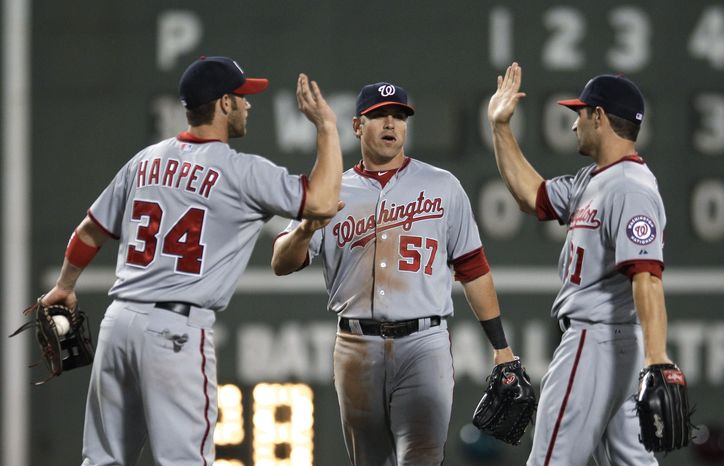 Washington Nationals right fielder Bryce Harper high-fives right fielder Xavier Nady, right, after the Nationals defeated the Boston Red Sox 7-4 at Fenway Park on Friday, June 8, 2012, in Boston. Harper went 3-for-5 with a home run and three RBI. (AP Photo/Charles Krupa)