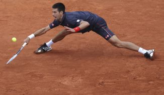 Novak Djokovic of Serbia returns in the men's final match against Rafael Nadal of Spain at the French Open tennis tournament in Roland Garros Stadium in Paris on Sunday, June 10, 2012. The match was suspended until Monday because of rain. (AP Photo/David Vincent)