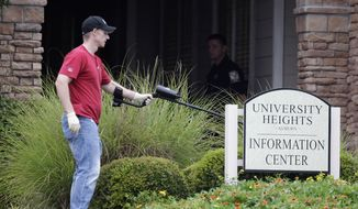 An investigator uses a metal detector to search for evidence at the scene of an overnight shooting at an apartment complex in Auburn, Ala., on Sunday, June 10, 2012. (AP Photo/David Goldman)
