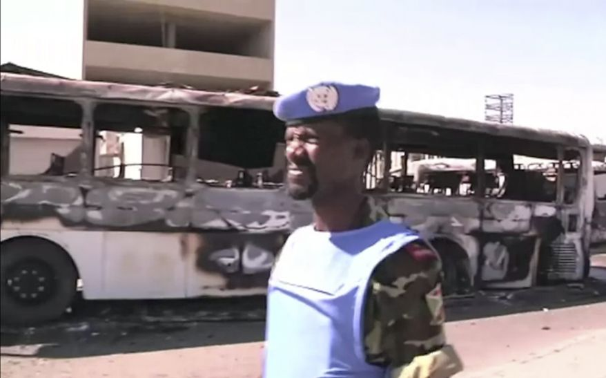 This image made from video released by the United Nations Supervision Mission in Syria (UNSMIS) and accessed on Saturday, June 9, 2012, purports to show a U.N. observer near a destroyed bus after overnight fighting in Damascus, Syria. (AP Photo/UNSMIS via AP Video)