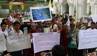 Buddhist monks and ethnic Rakhine people hold placards at the Shwedagon Pagoda, Myanmar's most revered Buddhist shrine, in Yangon, Myanmar, on Sunday, June. 10, 2012. The group gathered to say prayers for a murdered girl and others killed in the clashes in Rakhine state over the weekend. (AP Photo/Khin Maung Win)