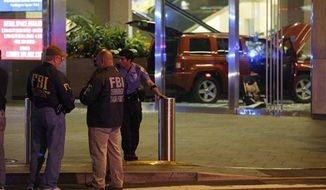 Members of the FBI Terrorism Task Force and police are on the scene after a sports utility vehicle crashed into an office building at 1050 Connecticut Avenue NW in Washington, Friday, June 8, 2012. According to news reports, police said the vehicle was intentionally driven into the building and the driver and the interior of the car was doused in gasoline.(AP Photo/Charles Dharapak)