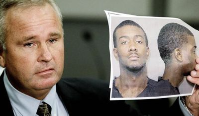 Auburn, Ala., police Chief Tommy Dawson displays a photo of Desmonte Leonard, 22, of Montgomery, Ala., who is wanted on capital-murder charges. Chief Dawson said authorities were looking for two other people of interest in connection with a deadly fight Saturday at an apartment complex. (Associated Press)