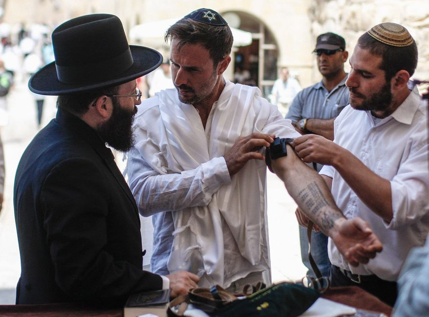 David Arquette (center) celebrates his bar mitzvah at the Western Wall, the holiest site where Jews can pray, in Jerusalem's Old City on Monday. Mr. Arquette came to shoot a segment for his travel show and ended up having a bar mitzvah and completing the Jewish rite of passage in Jerusalem. (Associated Press)