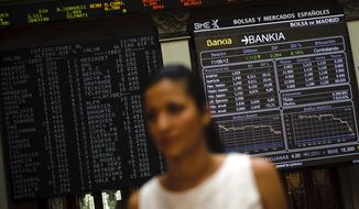 A journalist stands live June 11, 2012, on TV in front of the Stock Exchange's main display in Madrid as it shows Bankia values. (Associated Press)