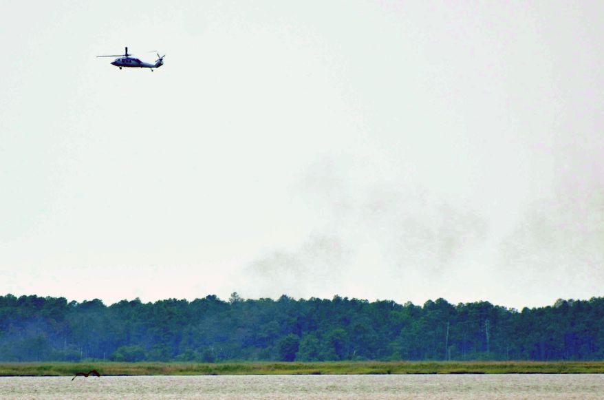 A military helicopter circles the area where an unmanned Navy aircraft crashed near Nanticoke, Md., on Monday, June 11, 2012. (AP Photo/The Daily Times, Steve Dickerson)