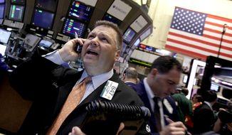 Trader George Ettinger (left) works June 11, 2012, on the floor of the New York Stock Exchange. (Associated Press)