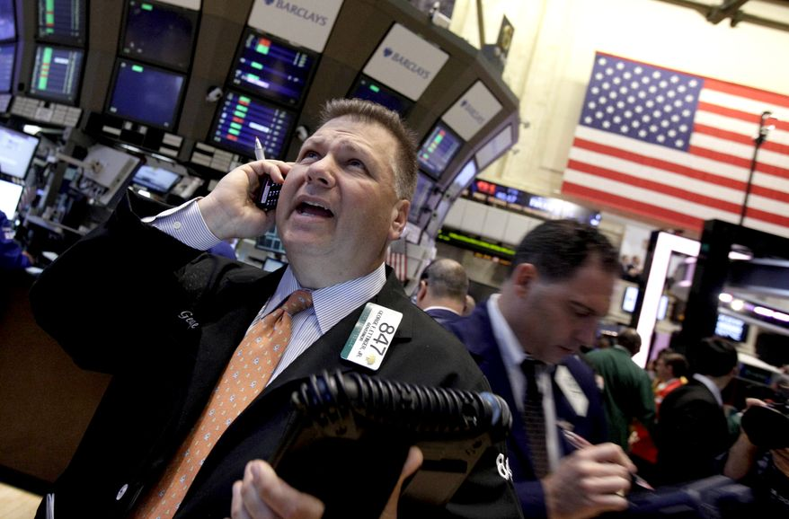 Trader George Ettinger (left) works June 11, 2012, on the floor of the New York Stock Exchange. (Associated Press)