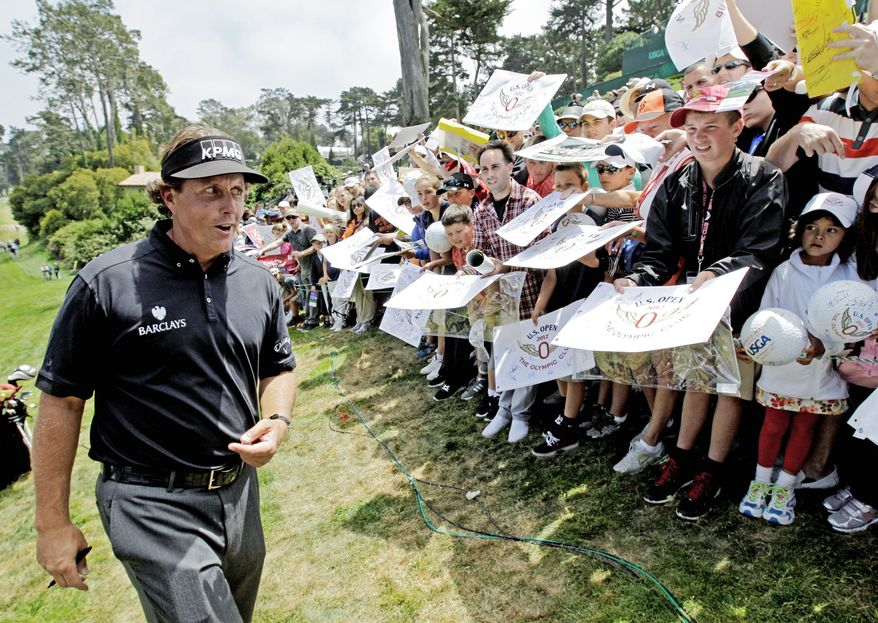 ** FILE ** In this file photo from June 2012, Phil Mickelson, signs for fans after a practice round. (Associated Press)