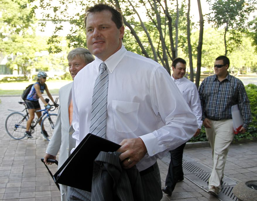 Former professional baseball pitcher Roger Clemens, accompanied by his attorney Rusty Hardin (left), arrives June 11, 2012, at federal court in Washington for his perjury trial. (Associated Press)
