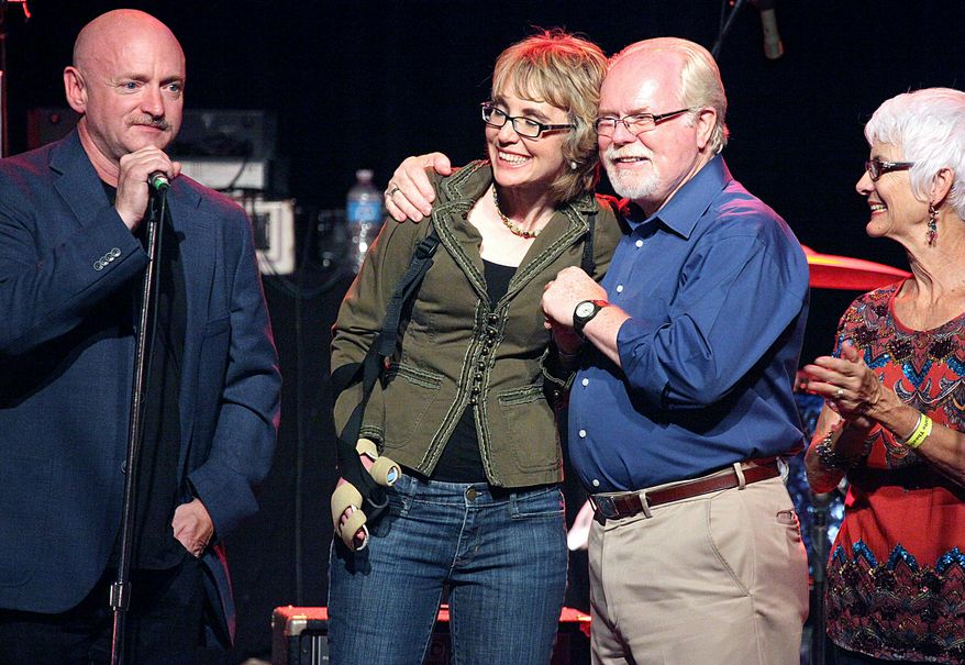 Former astronaut Mark Kelly (from left), former Rep. Gabrielle Giffords, Ron Barber and Nancy Barber gather during a get-out-the-vote rally for Mr. Barber at the Rialto Theater in downtown Tucson, Ariz., on Saturday, June 9, 2012. (AP Photo/Arizona Daily Star, Mamta Popat)