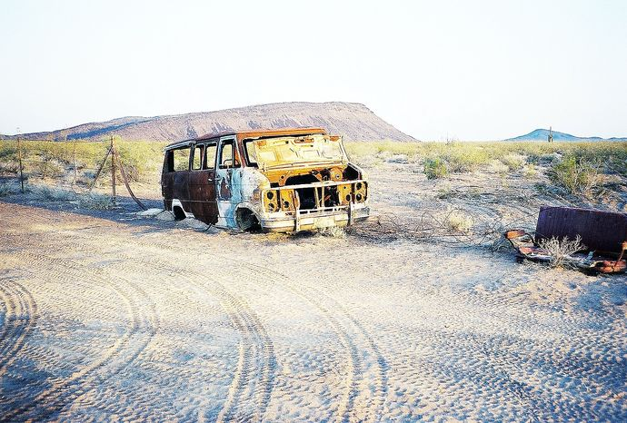 **FILE** A burned-out van sits in an Arizona wildlife refuge near Mexico, revealing an ominous dimension of cross-border human trafficking. (Associated Press)
