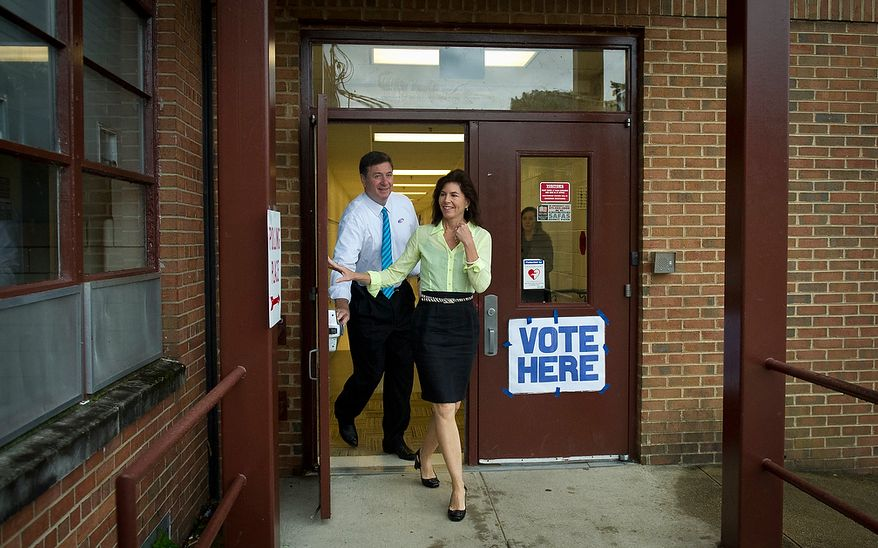 Former Virginia Governor and Republican U.S. Senate candidate George Allen and his wife Susan make their exit en route to the next precinct to visit voters, after casting their votes in the Republican Primary at Washington Mill Elementary School in Alexandria, Va., Tuesday, June 12, 2012. (Rod Lamkey Jr/The Washington Times)
