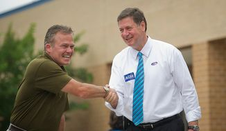 George Allen (right), a former Virginia governor and U.S. senator, greets voter Rod Wood of Fairfax Station at the Silver Brook Elementary School precinct in Fairfax Station on Tuesday, June 12, 2012. Mr. Allen is running in the Virginia's Republican primary in an effort to reclaim the Senate seat he lost to Jim Webb, a Democrat, in 2006. (Rod Lamkey Jr./The Washington Times)