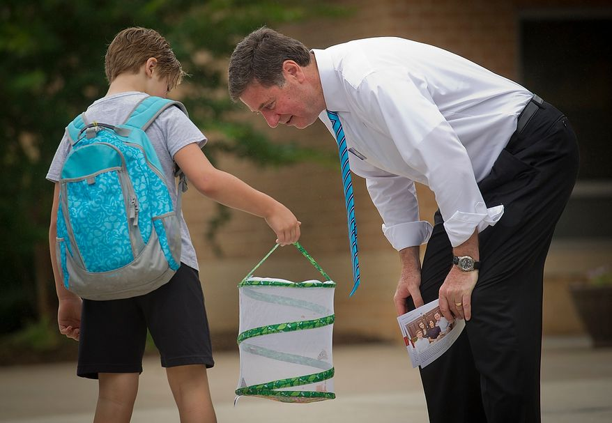 Former Virginia Governor and Republican U.S. Senate candidate George Allen takes a look at student's butterfly collection as he greets kids arriving to school at the Silver Brook Elementary School precinct in Fairfax Station, Va., Tuesday, June 12, 2012. (Rod Lamkey Jr/The Washington Times)