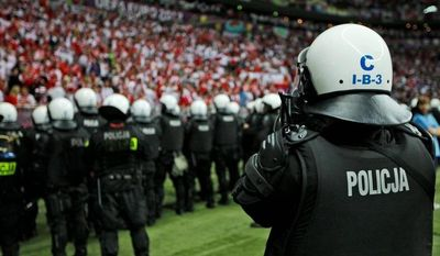 Polish police form a line at the pitch after the Euro 2012 match between Poland and Russia in Warsaw, Poland. Fifteen people were injured and more than 100 detained in violent clashes before the match. (Associated Press)