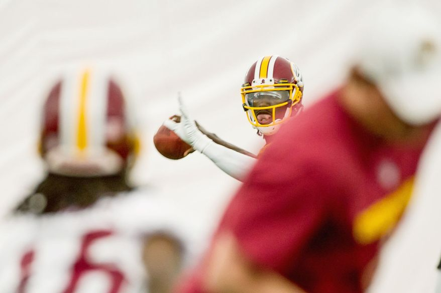 Redskins rookie quarterback Robert Griffin III steps back to throw during an organized team activity at Redskins Park in Ashburn, Va., on Tuesday, June 12, 2012. (Andrew Harnik/The Washington Times) (Andrew Harnik/The Washington Times)