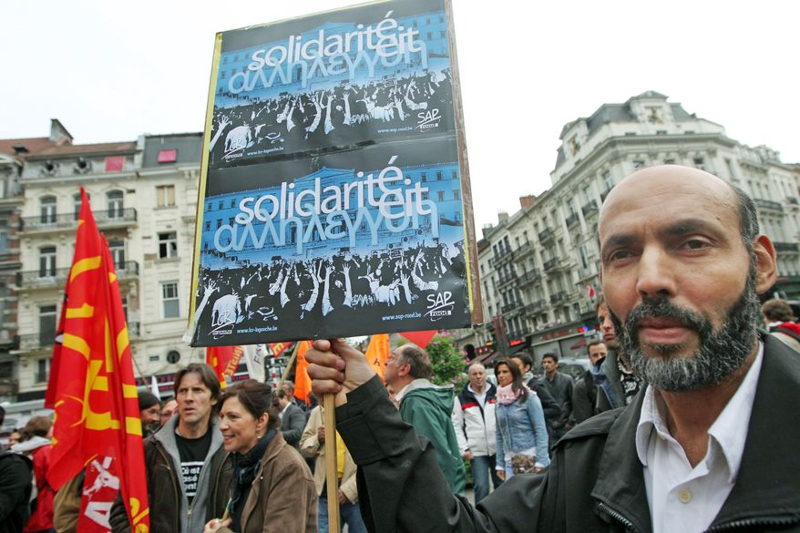 A man shows a poster as he stages a rally in solidarity with the Greek people against the austerity imposed by the EU and the IMF, in downtown Brussels, Wednesday, June 13, 2012. Poster reads: 'Solidarity' in Dutch, French and Greek. (AP Photo/Yves Logghe)