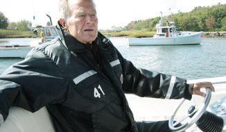 "Former President George H.W. Bush takes the wheel of his boat in Kennebunkport, Maine, during the filming of the documentary ""41,"" which premieres Thursday on HBO. (HBO via Associated Press)"