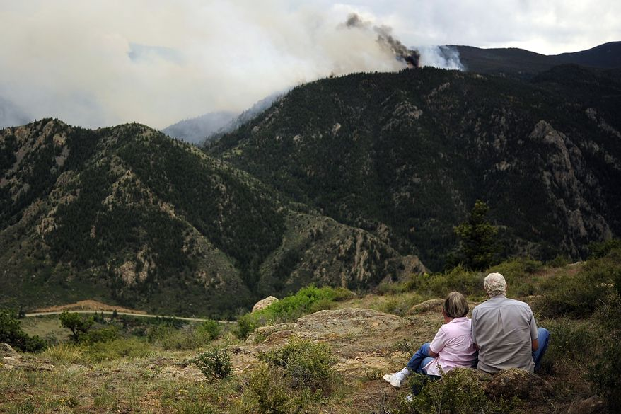 Art and Carrol Newburn watch  June 12, 2012, from Glacier View Meadows as the High Park fire burns west of Fort Collins, Colo. The fire has now burned more than 40,000 acres, encompassing more than 65 square miles. (Associated Press/The Denver Post)