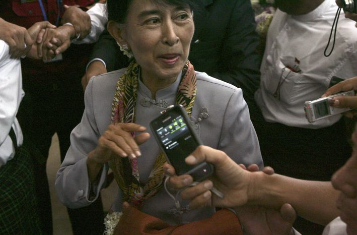 Myanmar opposition leader Aung San Suu Kyi talks to reporters as she arrives at Yangon International Airport on Wednesday, June 13, 2012, in Yangon, Myanmar, on her way to Europe for the first time in 24 years. (AP Photo)