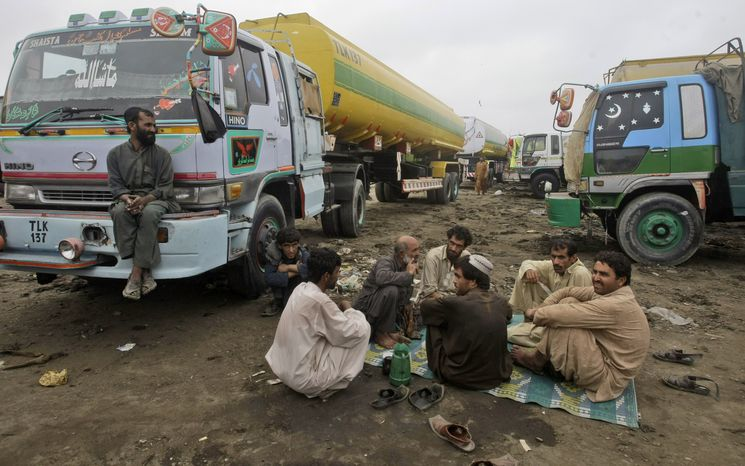 Pakistani oil tanker drivers sit June 6, 2012, next to their tankers in a compound in Karachi, Pakistan. The tankers were used to transport NATO fuel supplies to Afghanistan. (Associated Press)