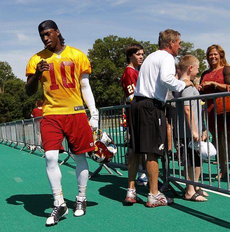 Washington Redskins quarterback Robert Griffin III, left, walks past head coach Mike Shanahan, right, following NFL football practice at Redskins Park in Ashburn, Va., Wednesday, June 13, 2012. (AP Photo/Pablo Martinez Monsivais)