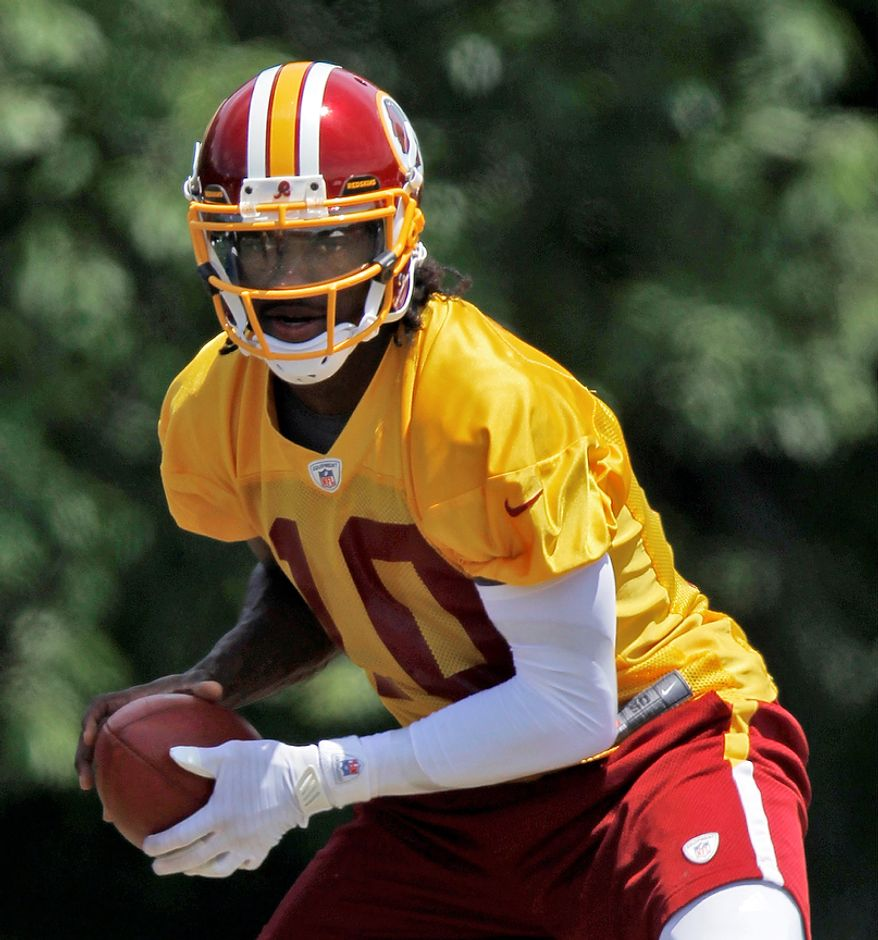 Redskins rookie quarterback Robert Griffin III works during a drill during an organized team activity at Redskins Park in Ashburn, Va, on Tuesday, June 12, 2012. (Andrew Harnik/The Washington Times)