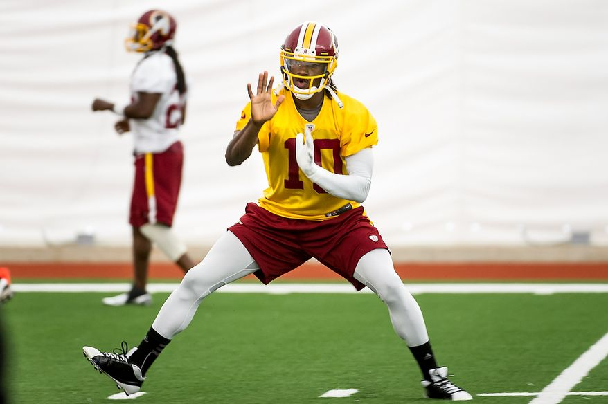 Washington Redskins quarterback Robert Griffin III (10) warms up before practice at the team's indoor training facility during mini camp at Redskins Park, Ashburn, Va., Tuesday, June 12, 2012. (Andrew Harnik/The Washington Times)