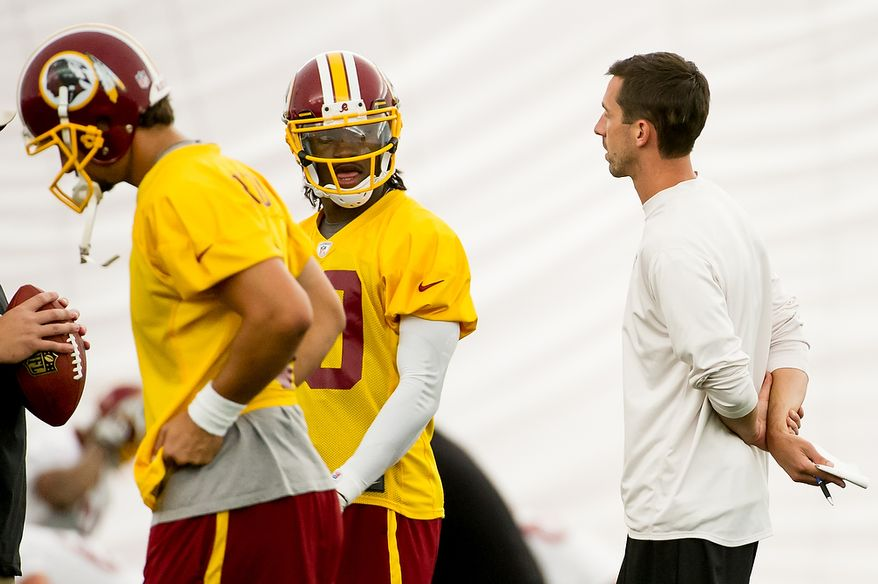 Washington Redskins quarterback Robert Griffin III (10), second from left, speaks with Washington Redskins offensive coach Kyle Shanahan, right, in the team's indoor training facility during mini camp at Redskins Park, Ashburn, Va., Tuesday, June 12, 2012. (Andrew Harnik/The Washington Times)