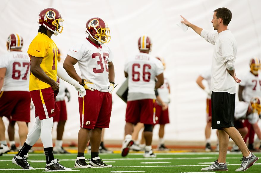 Washington Redskins quarterback Robert Griffin III (10), left, and Washington Redskins full back Darrel Young (36), second from left, take direction from Washington Redskins offensive coach Kyle Shanahan, right, in the team's indoor training facility during mini camp at Redskins Park, Ashburn, Va., Tuesday, June 12, 2012. (Andrew Harnik/The Washington Times)