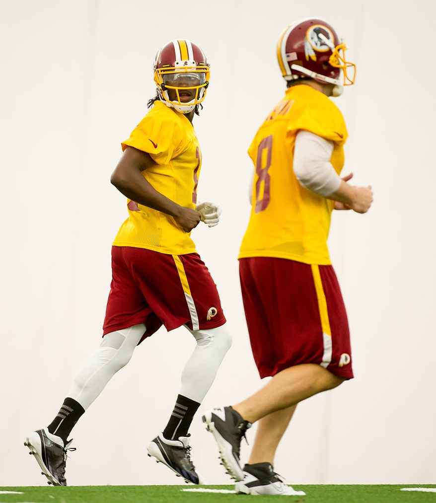 Washington Redskins quarterback Robert Griffin III (10), left, and Washington Redskins quarterback Rex Grossman (8), right, jog to a team drill in the team's indoor training facility during mini camp at Redskins Park, Ashburn, Va., Tuesday, June 12, 2012. (Andrew Harnik/The Washington Times)