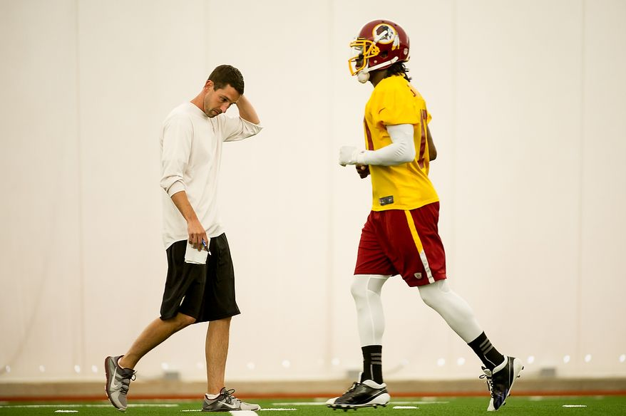 Washington Redskins quarterback Robert Griffin III (10), right, jogs by Washington Redskins offensive coach Kyle Shanahan, left, in the team's indoor training facility during mini camp at Redskins Park, Ashburn, Va., Tuesday, June 12, 2012. (Andrew Harnik/The Washington Times)