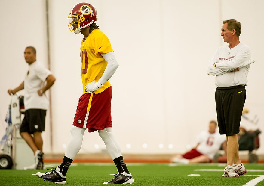 Washington Redskins quarterback Robert Griffin III (10), second from left, stands near Washington Redskins head coach Mike Shanahan, right, in the team's indoor training facility during mini camp at Redskins Park, Ashburn, Va., Tuesday, June 12, 2012. (Andrew Harnik/The Washington Times)