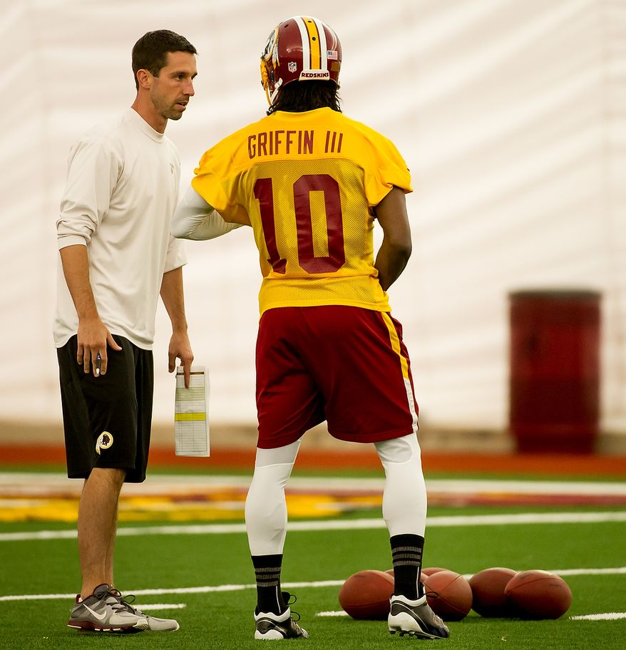 Washington Redskins quarterback Robert Griffin III (10), right, speaks with Washington Redskins offensive coach Kyle Shanahan, left, in the team's indoor training facility during mini camp at Redskins Park, Ashburn, Va., Tuesday, June 12, 2012. (Andrew Harnik/The Washington Times)