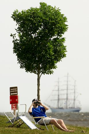 """George Keniston, of Silver Spring, Md., watches June 13, 2012, through binoculars at Sandy Point State Park in Annapolis, Md., as tall ships pass under the Chesapeake Bay Bridge en route to the Inner Harbor in Baltimore for a bicentennial commemoration of the War of 1812. The week-long """"Star-Spangled Sailabration"""" includes free tours of the ships, waterside festivities, an air show featuring the Blue Angels and the world premiere of """"Overture for 2012,"""" composed by Philip Glass. (Andrew Harnik/The Washington Times)"""