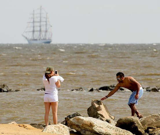 """Caroline Amaya (left), of Gaithersburg, Md., takes a photograph of her husband, Sergio, at Sandy Point State Park in Annapolis, Md., on June 13, 2012, as tall ships pass under the Chesapeake Bay Bridge en route to the Inner Harbor in Baltimore for a bicentennial commemoration of the War of 1812. The week-long """"Star-Spangled Sailabration"""" includes free tours of the ships, waterside festivities, an air show featuring the Blue Angels and the world premiere of """"Overture for 2012,"""" composed by Philip Glass. (Andrew Harnik/The Washington Times)"""